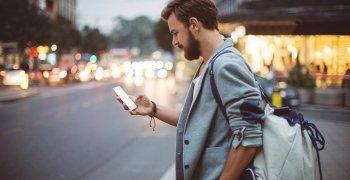 mies kadun varrella katsomassa puhelintaan