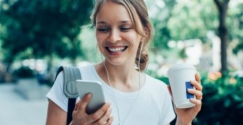 woman smiling holding her phone and a takeaway cup